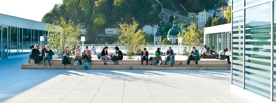 Eine Gruppe Studierende sitzt auf der Unipark Dachterrasse .