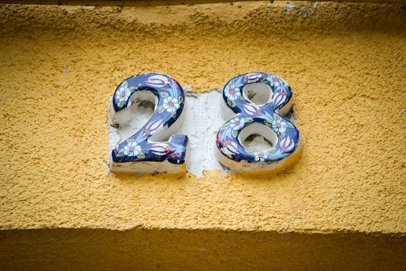 Eine bunte Hausnummer auf einer gelben Hauswand.