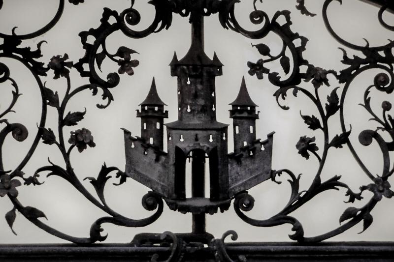 Verschnörkeltes Metallgitter mit einem Schloss im Zentrum