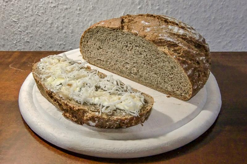 Tipps und Tricks in der Erkältungszeit – Hausmittel selbst gemacht: Ein bestrichenes Honig-Butter-Brot mit geriebenem Kren vor einem Brotlaib.