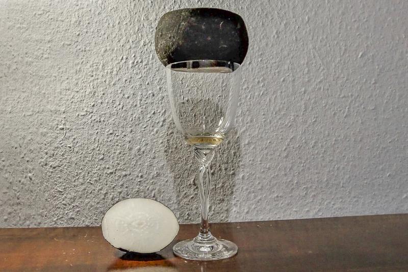 Tipps und Tricks in der Erkältungszeit – Hausmittel selbst gemacht: Ein vorbereiteter, schwarzer Rettich liegt auf einem Weinglas.