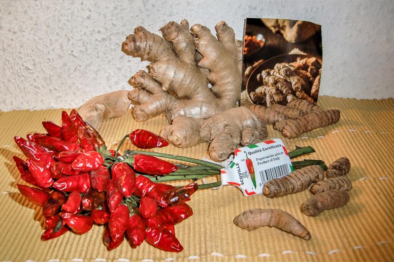 Auf einem hellorangen Untergrund liegen verschiedene Ingwerwurzeln, Kurkumawurzel-Stücke und ein Bund aus kleinen, roten Chilischoten.