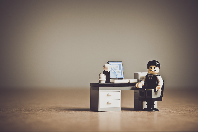 Prokrastination Legofigur verzweifelt am Arbeitsplatz