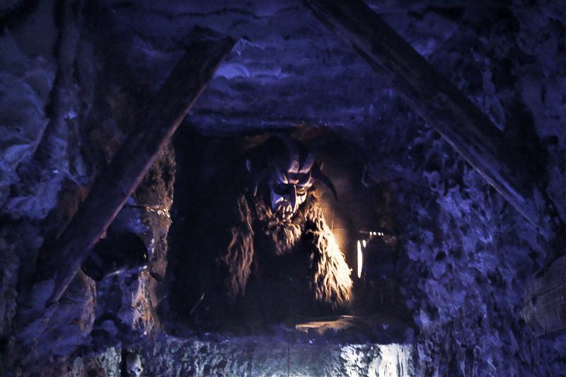 Der Krampus: Eine Krampusgestalt sitzt in einer Grotte im Kitzbüheler Krampusmuseum