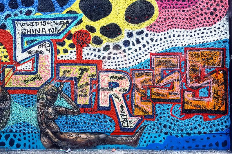 """Buntes Graffiti """"Stress"""" auf einer Mauer"""