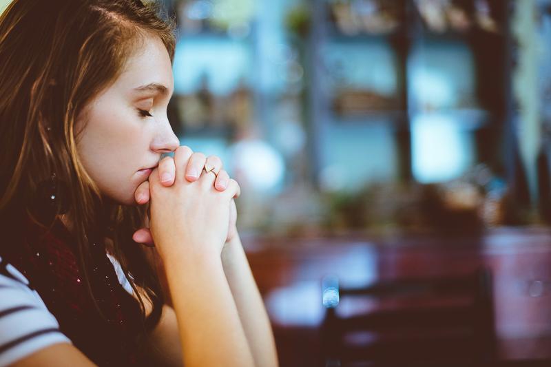 Theologiestudium: junge Frau betet
