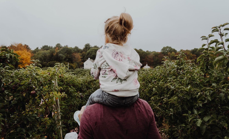 Mädchen sitzt bei ihrem Vater auf den Schultern