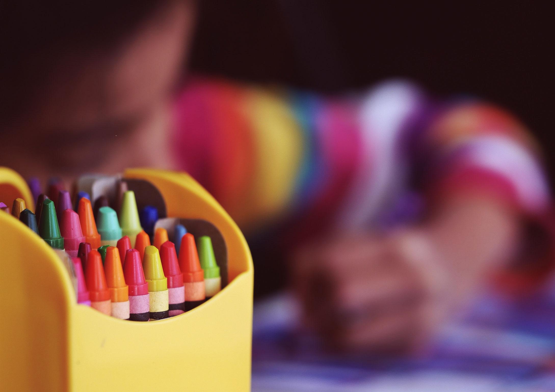 Kind malt mit Wachsmalkreiden