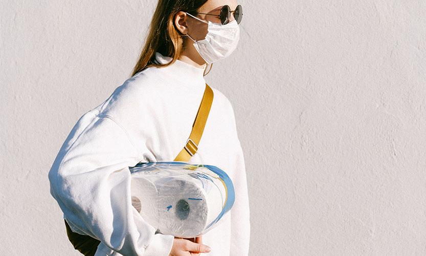 Frau mit Maske und Klopapier