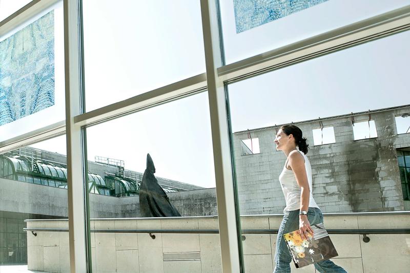 Studentin geht NaWi Glasfassade entlang