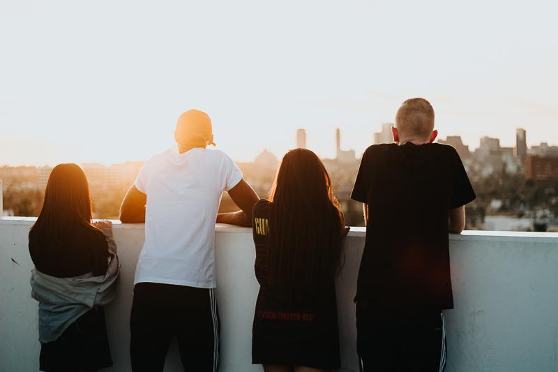 Jugendgruppe blickt von einer Dachterrasse in den Sonnenuntergang.