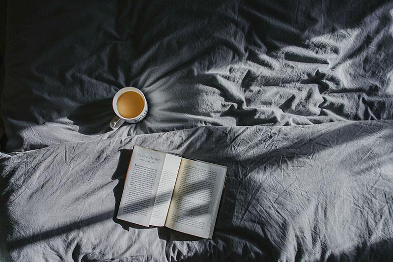 Buch liegt aufgeschlagen auf Bett