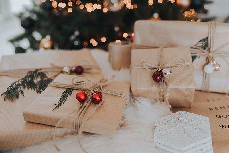 Sinnvolles Schenken: mehrere kleine Geschenke vor Weihnachtsbaum